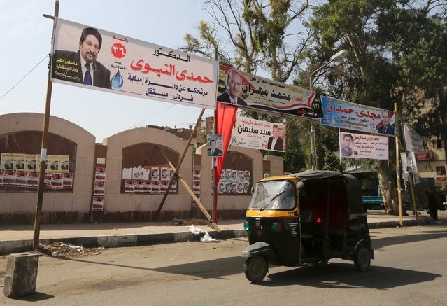 A man drives a three-wheeled vehicle beneath election campaign banners in the Imbaba district of Giza, Egypt, October 13, 2015. (Photo by Mohamed Abd El Ghany/Reuters)