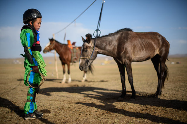 "This picture taken on July 10, 2015 shows 13-year-old jockey Purevsurengiin Togtokhsuren in his racing uniform as he awaits the ""Khyazaalan"" (four year old) horse race in Khui Doloon Khudag, some 50 kms west of Ulan Bator. (Photo by Johannes Eisele/AFP Photo)"