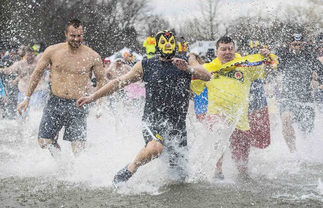 """Participants take part in Courage Polar Bear Dip at Coronation Park in Oakville, Canada January 1, 2015. This year's edition of the Courage Polar Bear Dip, in which hundreds of participants ran into Lake Ontario in subfreezing temperatures, will raise money for the """"Rwanda: Right to Clean Water"""" project. (Photo by Mark Blinch/Reuters)"""