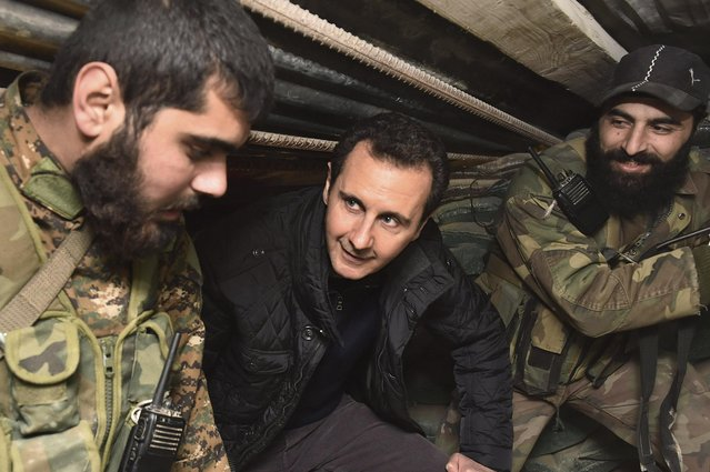 "Syrian President Bashar al-Assad (C) talks to soldiers during a visit to Jobar, northeast of Damascus, in this handout photograph distributed by Syria's national news agency SANA on January 1, 2015. Al-Assad visited a district on the outskirts of Damascus and thanked soldiers fighting ""in the face of terrorism"", his office said on its Twitter account on Wednesday, posting pictures of the rare trip. (Photo by Reuters/SANA)"