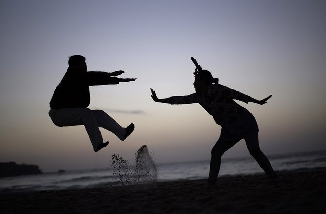 A couple acts out a martial-arts move for a friend's camera (not pictured) as they wait to welcome the first sunrise of 2015 on Sydney's Bondi beach at dawn, January 1, 2015. (Photo by Jason Reed/Reuters)