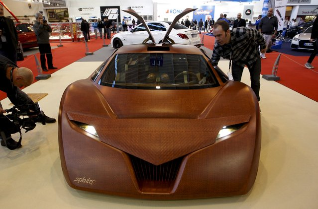 "Joe Harmon (R), designer of the ""Splinter"", a concept car made for 90 percent of wood composites, looks at his car at the Essen Motor Show in Essen, Germany, November 27, 2015. (Photo by Ina Fassbender/Reuters)"