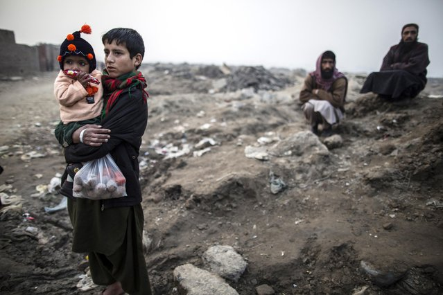 A teenage boy carries his sibling in a slum on the outskirts of Lahore January 12, 2015. (Photo by Zohra Bensemra/Reuters)