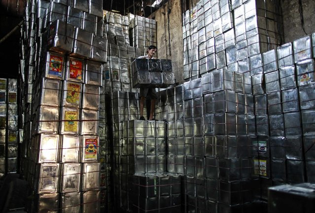 A labourer takes down tin boxes inside a tin container recycling factory in a slum area in Mumbai January 12, 2015. India's industrial output recovered at a much faster-than-expected pace in November, posting an annual growth of 3.8 percent year-on-year, helped by a rebound in capital goods sector, government data showed on Monday. (Photo by Danish Siddiqui/Reuters)