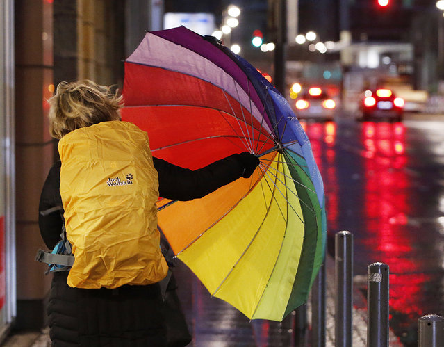A woman fights with her colorful umbrella as she walks in the city center of Frankfurt, Germany, on a stormy Thursday, January 18, 2018. Heavy storms are forecasted for most parts of Germany on Thursday. (Photo by Michael Probst/AP Photo)