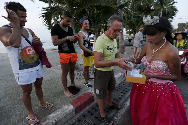 An activists hands out condoms to tourists during a march through Pattaya resort town to raise awareness on the World Aids Day in Pattaya, east of Bangkok, Thailand December 1, 2015. (Photo by Chaiwat Subprasom/Reuters)