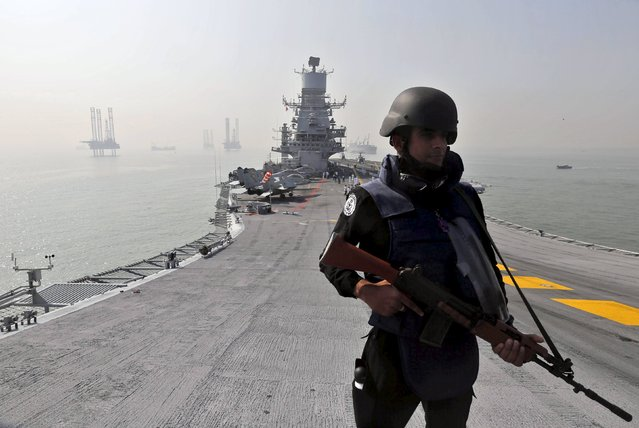 An Indian Navy personnel stands guard during a media preview on the flight deck of INS Vikramaditya, Indian Navy's aircraft carrier, anchored in the Arabian Sea off the coast of Mumbai, India, December 3, 2015. The tour was organised by Indian Navy on the eve of its Navy Day celebrations. (Photo by Shailesh Andrade/Reuters)