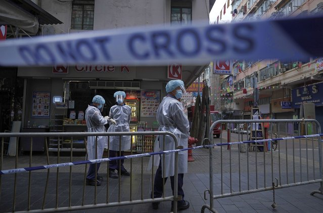 Government workers wearing personal protective equipment stand guard at the closed area in Jordan district, in Hong Kong, Sunday, January 24, 2021. Thousands of Hong Kong residents were locked down Saturday in an unprecedented move to contain a worsening outbreak in the city, authorities said. (Photo by Vincent Yu/AP Photo)
