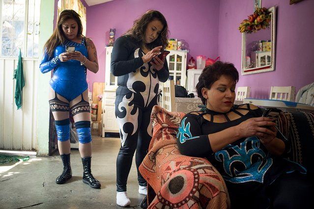 Luchadoras check their phones at Juliza's home. (Photo by Diana Bagnoli/The Washington Post)