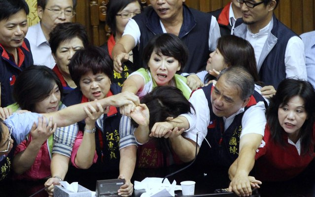 Legislators from Taiwan's ruling Kuomintang party and opposition try to seize the parliament's podium on June 25, 2013. Fighting broke out in Taiwan's parliament as legislators scuffled and threw coffee during a debate on whether a controversial capital gains tax on share trading should be revised less than a year after it was brought in. (Photo by AFP Photo)