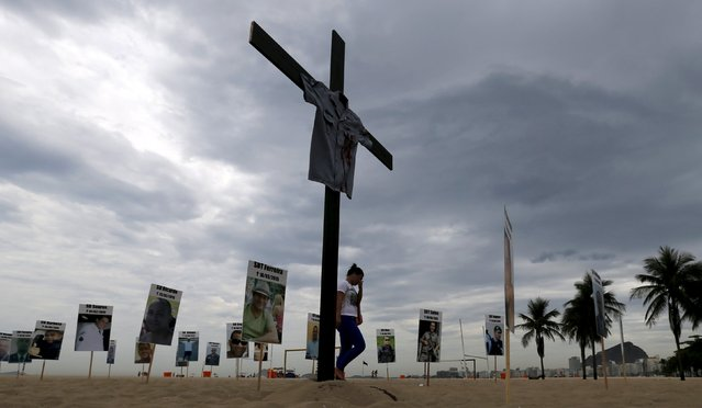 A relative of a police officer walks among pictures planted by the NGO Rio de Paz (Peace Rio) on Copacabana beach, in memory of police officers killed in Rio de Janeiro, December 10, 2015. (Photo by Sergio Moraes/Reuters)