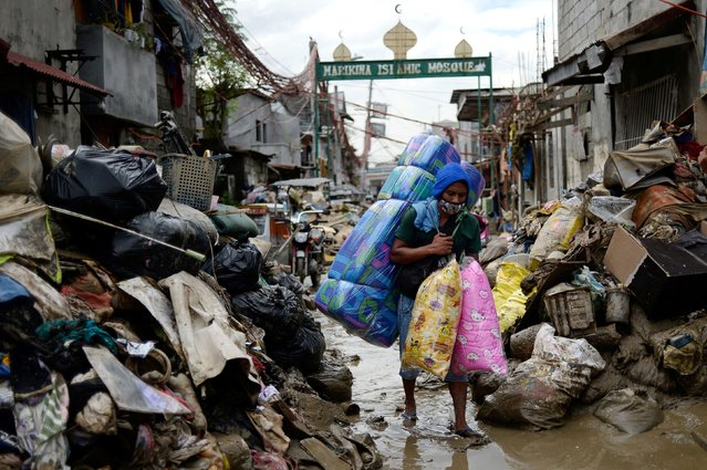 A man selling pillows and mattresses walks past debris from the flood brought by Typhoon Vamco, in Marikina, Metro Manila, Philippines, November 16, 2020. (Photo by Lisa Marie David/Reuters)