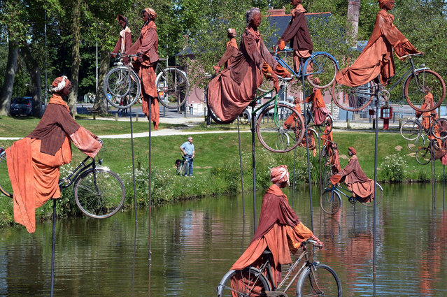 """A photo taken on July 1, 2013 shows a sculpture by French artist Guy Lorgeret, entitled """"Retour a Betton"""" (""""Return to Betton""""), in Betton, a suburb of the western French city of Rennes. The sculpture represents people on bicycles migrating from a bank to another, claiming their freedom, like their refusal to compete. (Photo by Damien Meyer/AFP Photo)"""