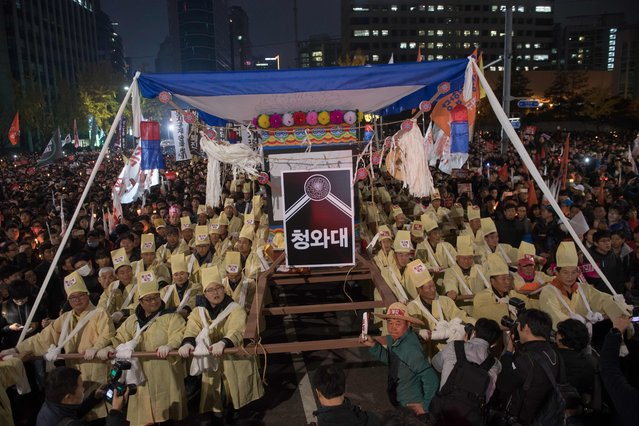 Protesters stage a mock funeral for South Korean President Park Geun-Hye an anti-government protest in central Seoul on November 12, 2016. (Photo by Ed Jones/AFP Photo)
