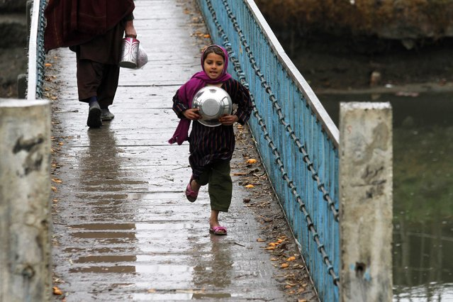 A girl with a bowl runs over a bridge after a rain on the outskirts of Peshawar January 22, 2015. (Photo by Fayaz Aziz/Reuters)