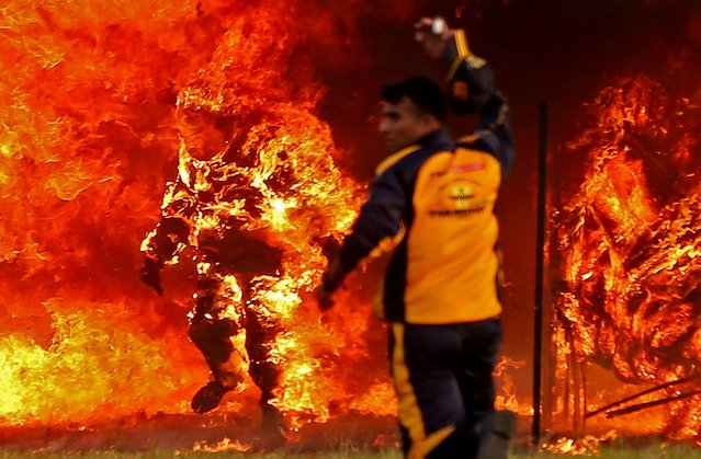 "Member of the Indian Army Jawans (soldiers) Captain Shivam Singh (L) belonging to the ""ASC Tornadoes"" daredevil bike team comes out from the fire after his bike skidded during a world record attempt for the ""Longest ride through tunnel of fire"" held at ASC centre & College in Bangalore, India, 10 November 2020. According to the report, the record was achieved by Shivam Singh through tunnel fire recording 127 meters and the existing record was 120.40 meter by Enrico Schoeman and Andre de Kock both from South Africa on 05 September 2014. (Photo by Jagadeesh N.V./EPA/EFE)"