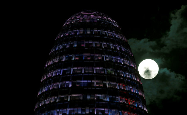 The supermoon rises behind the Agbar Tower in Barcelona, Spain November 14, 2016. (Photo by Albert Gea/Reuters)