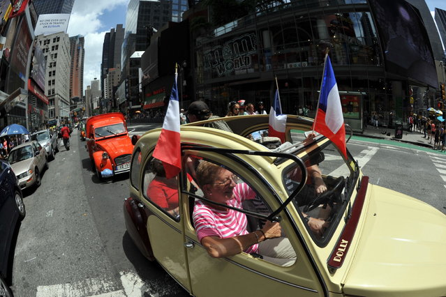 A parade of Citroen 2CV cars from the Greater New York Citroen and  Velosolex Touring Club passes through Time's Square on Bastille Day July 14, 2013 in New York. (Photo by Stan Honda/AFP Photo)
