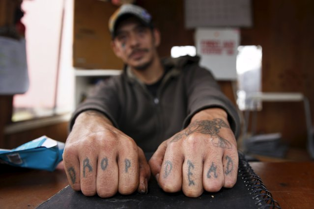"Gary Dumo, 36, shows his tattoos while working security at the homeless tent encampment Nickelsville in Seattle, Washington October 13, 2015. ""I'd love to see myself in a home, with working power, electricity, walls and air-conditioned. I'm pretty sure there are more people though that need a place to stay"", Dumo said. (Photo by Shannon Stapleton/Reuters)"