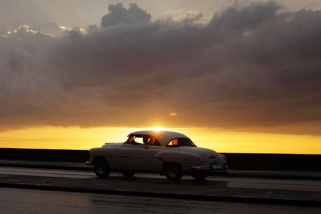 """A U.S.-made private collective taxi drives down Havana's seafront boulevard """"El Malecon"""" during sunset, on July 15, 2013. (Photo by Desmond Boylan/Reuters)"""