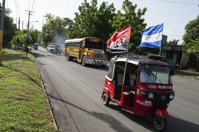 A moto-taxi decorated with a Sandinista National Liberation Front political party banner and a Nicaraguan national flag, takes part in a caravan ahead of a rally commemorating the uprising that ousted the Anastasio Somoza family, in Managua, Nicaragua, Thursday, July 19, 2018. Nicaragua marked the 39th anniversary of the 1979 revolution against the dictator Somoza on Thursday amid protest and bloodshed. (Photo by Cristobal Venegas/AP Photo)