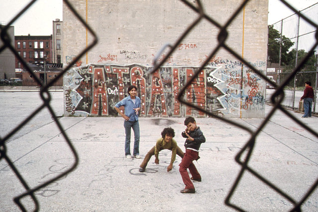 """Children play in front of """"A Train"""" graffiti in Brooklyn's Lynch Park, in June of 1974. (Photo by Danny Lyon/NARA via The Atlantic)"""