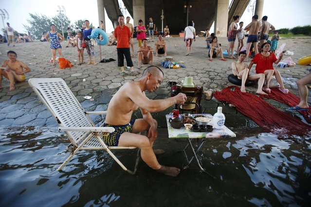 A man sitting on a beach chair in his swimming trunks takes his meal at a small table partially dipped into the Hanjiang river to escape the summer heat, as other swimmers look on under a bridge in Wuhan, Hubei province July 28, 2013. The highest temperature in Wuhan reached 37 degrees Celsius (98.6 degrees Fahrenheit) on Sunday, local media reported. Picture taken July 28, 2013. (Photo by Reuters/China Daily)