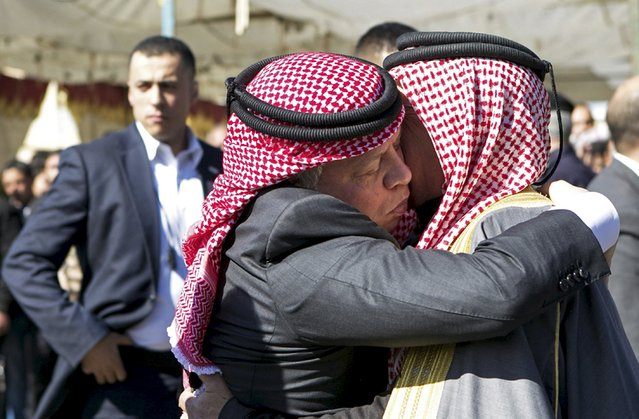 Jordan's King Abdullah (L) offers his condolences to Safi al-Kasaesbeh, the father of Jordanian pilot Muath al-Kasaesbeh, at the headquarters of the family's clan in the city of Karak, Jordan February 5, 2015. (Photo by Reuters/Petra News Agency)