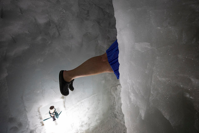 Ice swimmer Rene climbs through an ice hole as he is on his way to swim in a filled up water kettle in an ice cave inside the Nature Ice Palace, with a hight of 3,250 meters (10,663 feet) above sea level, at Hintertux Glacier near Hintertux, some 480 kilometers (298 miles) western of Vienna, Austria, 27 July 2018. (Photo by Christian Bruna/EPA/EFE)