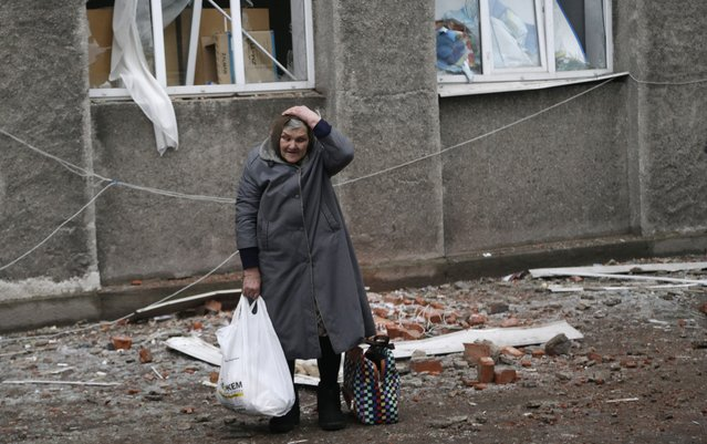 An elderly woman holds her head after collecting supplies of humanitarian aid in the town of Debaltseve, Ukraine, Friday, February 6, 2015. (Photo by Petr David Josek/AP Photo)