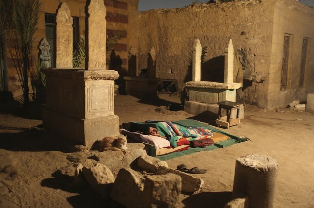 A man sleeps between tombstones in front of his single-room home on a hot night in the Cairo Necropolis, Egypt, October 13, 2015. (Photo by Asmaa Waguih/Reuters)