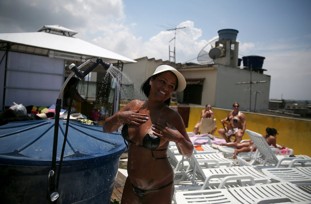 A woman takes a shower as she takes her masking tape bikini off after sunbathing on a terrace at the Erika Bronze spa in Rio de Janeiro, Brazil, November 22, 2016. (Photo by Pilar Olivares/Reuters)