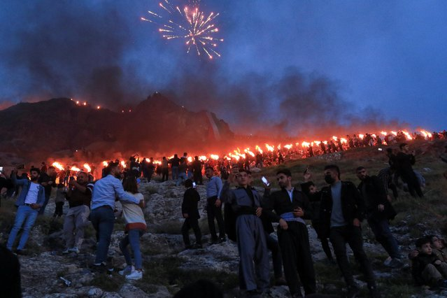 Iraqi Kurdish people carry fire torches, as they celebrate Nowruz Day, a festival marking the first day of spring and the new year, in the town of Akra near Duhok, in Iraqi Kurdistan, Iraq on March 20, 2021. (Photo by Ari Jalal/Reuters)