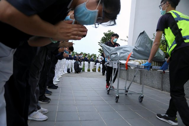 Members of the Tzu Chi Foundation pay their respects as rescuers transfer bodies at Xincheng railway station after a train derailed in a tunnel north of Hualien, Taiwan on April 2, 2021. (Photo by Annabelle Chih/Reuters)