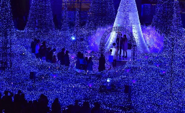 "People admire illuminations featuring the theme of ""Canyon d'Azur"" (Blue Canyon) at Caretta Illumination in Tokyo on November 20, 2016. The illuminations with 270,000 LED lights will be displayed until February 14, 2017. (Photo by Kazuhiro Nogi/AFP Photo)"