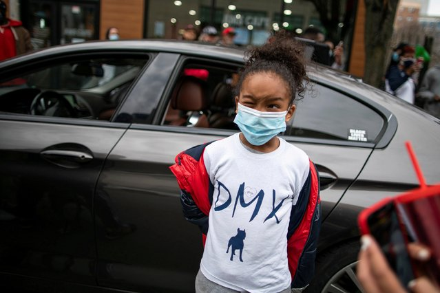 A child poses for pictures as people visit a makeshift memorial for musician and actor DMX outside White Plains Hospital, after he died at the age of 50, in White Plains, New York, U.S., April 9, 2021. (Photo by Eduardo Munoz/Reuters)
