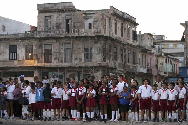 Schoolchildren wait on a roadside for the military vehicles transporting the ashes of Cuba's late President Fidel Castro at the start of a three-day journey to the eastern city of Santiago, in Havana, Cuba, November 30, 2016. (Photo by Carlos Garcia Rawlins/Reuters)