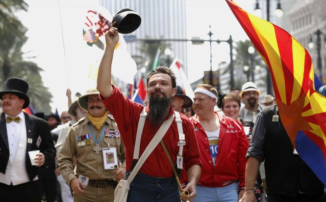 Alexander Fleming of New Orleans tips his hat to the crowd on Canal Street during a parade which wound its way through the French Quarter kicking off the fourth annual Just For Men National Beard and Moustache Championships Saturday, September 7, 2013 in New Orleans. Contestants competed in 18 different categories including Dali, full beard natural and sideburns. (Photo by Susan Poag/AP Photo)