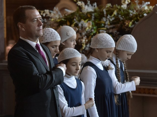 Russian Prime Minister Dmitry Medvedev, left, crosses himself as he attends the midnight Christmas Mass in the Christ the Savior Cathedral in Moscow, Wednesday, January 6, 2016. Orthodox Christians celebrate Christmas on Jan. 7, in accordance with the Julian calendar. (Photo by Alexander Astafyev, Sputnik, Government Pool Photo via AP Photo)
