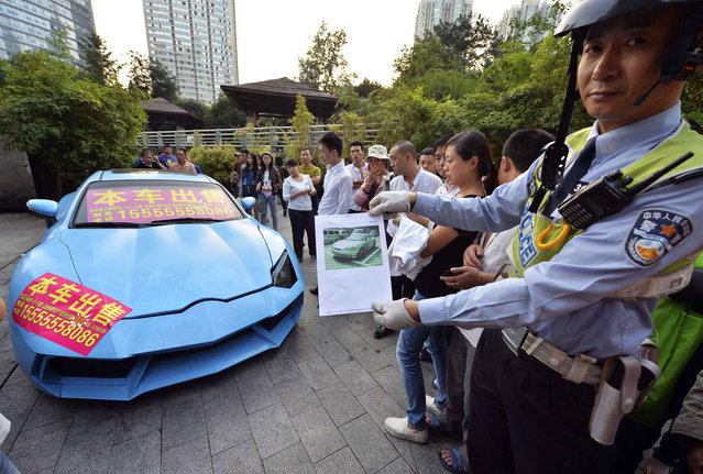 """A policeman shows a paper bearing a registration photo of a Hyundai Coupe car which was later refitted into a knockoff Lamborghini (L) parked on a pedestrian street in Chongqing municipality, September 12, 2013. Police towed the car away on the charge of illegal parking on Thursday after failing to contact the owner. A placard under the car windshield reads, """"This refitted Lamborghini car on sale, starting price 98,000 yuan (16,018 USD)"""", local media reported. (Photo by Reuters/Stringer)"""