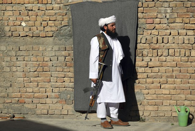 Mofti Noman's house guard stand in front of his home near the mosque after a bomb explosion in Shakar Dara district of Kabul, Afghanistan, Friday, May 14, 2021. A bomb ripped through a mosque in northern Kabul during Friday prayers killing 12 worshippers, Afghan police said. (Photo by Rahmat Gul/AP Photo)