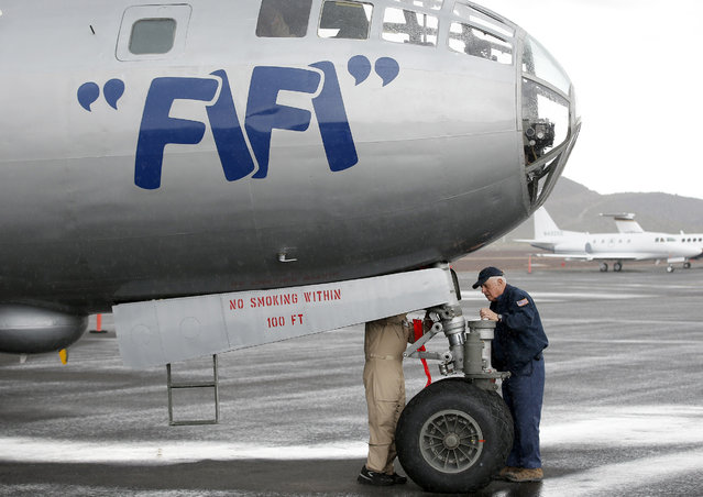 """Buzz Perez, left, of the Commemorative Air Force, gets some help frOm Jack Coughlin as the two stand near the front landing gear of the CAF's World War II era B-29 Superfortress bomber plane """"FIFI"""" after it arrived at Deer Valley Airport, Monday, February 23, 2015, in Phoenix. (Photo by Ross D. Franklin/AP Photo)"""