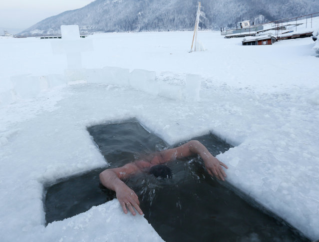 A member of the local yacht club, Boyarintsev immerses himself in the waters of ice-covered Yenisei River, in the air temperature about minus 25 degrees Celsius (minus 13 degrees Fahrenheit), outside Krasnoyarsk, Siberia, Russia, January 19, 2016. Orthodox believers mark Epiphany on January 19 by immersing themselves in icy waters regardless of the weather. (Photo by Ilya Naymushin/Reuters)