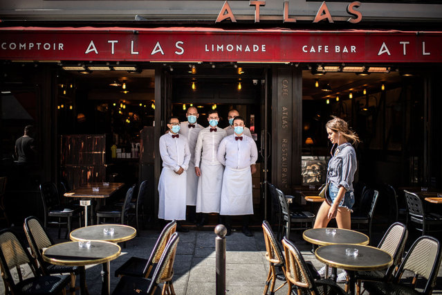Waiters pose at their terrace of their restaurant rue de Buci in Paris on June 2, 2020, as cafes and restaurants reopen in France, while the country eases lockdown measures taken to curb the spread of the COVID-19 (the novel coronavirus). (Photo by Martin Bureau/AFP Photo)