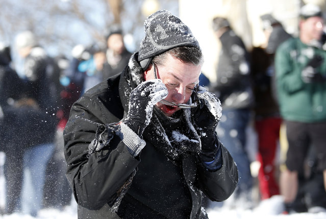 A man reacts after being hit in the face with a snowball during an organized snowball fight at Dupont Circle Sunday, January 24, 2016 in Washington. (Photo by Alex Brandon/AP Photo)