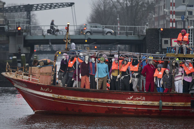Amnesty International activists protest against the ongoing migrant crisis with a boat filled with mannequins wearing life vests outside the Maritime Museum, rear, during an informal meeting of EU Justice and Home Affairs ministers at the Maritime Museum in Amsterdam, Netherlands, Monday, January 25, 2016. European Union justice and interior ministers have started urgent discussions on how to tackle the migrant crisis amid the stream of new arrivals and continuing disagreements over how to seal off borders. (Photo by Peter Dejong/AP Photo)
