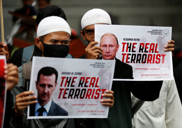 Muslim men hold placards during a protest calling for an end to the violence in Aleppo, Syria outside the Russian embassy in Jakarta, Indonesia December 19, 2016. (Photo by Darren Whiteside/Reuters)