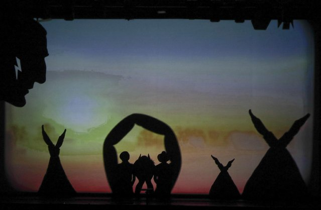 """In this photo taken on Tuesday, December 20, 2016, dancers of the U.S. company """"Catapult"""" create an Indian camp, during their show """"Magic Shadows"""", in Milan, Italy. (Photo by Luca Bruno/AP Photo)"""
