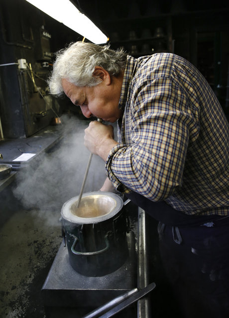 Serge Huguenin of the Blondeau foundry blows lycopodium out of a mould for a bell in La Chaux-de-Fonds, Switzerland January 19, 2016. (Photo by Denis Balibouse/Reuters)