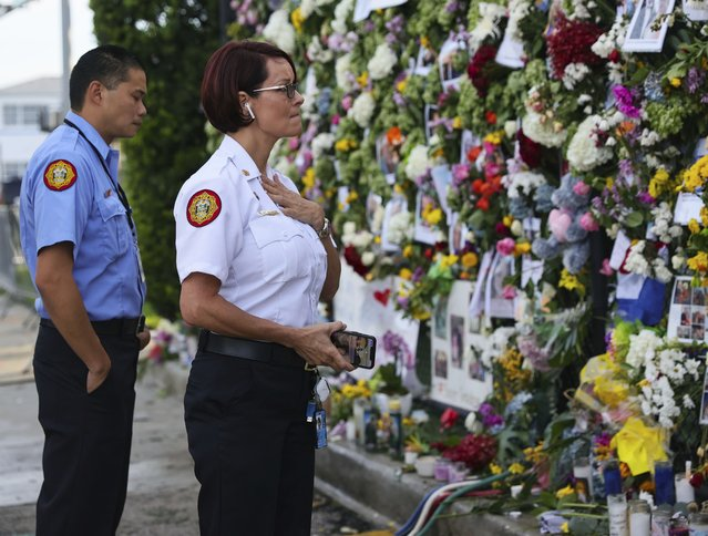 From left, Miami-Dade Fire Rescue personnel Fai Yeung and Chief Melanie C. Adams visit the makeshift memorial setup near the partially collapsed 12-story Champlain Towers South Condo in Surfside, Fla., Thursday, July 1, 2021. Search is paused because of structural concerns officials say. The apartment building partially collapsed on Thursday, June 24. (Photo by David Santiago/Miami Herald via AP Photo)